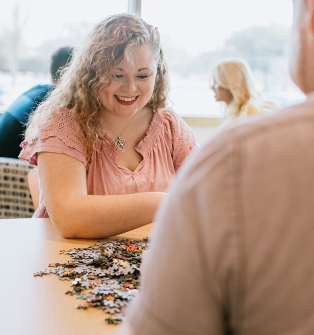 woman and man happily completing puzzle