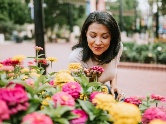 A woman smells flowers outdoors