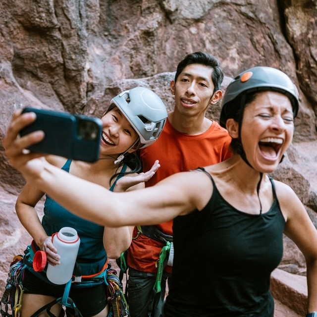 A group of rock climbers taking a selfie and laughing together