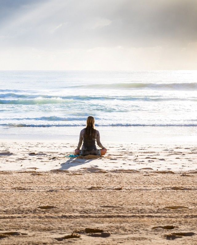 A woman is meditating on a beach