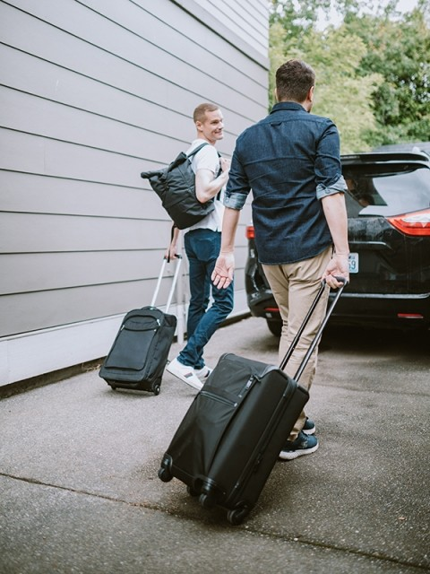 Two men walking to a car with suitcases
