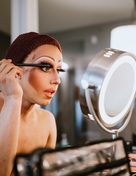 LGBTQ advocate Eric Dorsa is doing their makeup to get into drag.