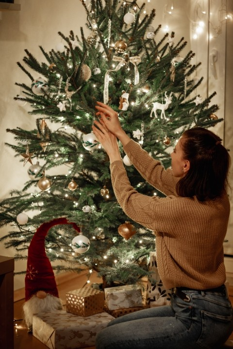 A woman is hanging ornaments on a tree